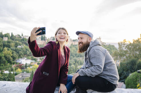 Happy couple taking a selfie with Alhambra in background, Granada, Spain - DGOF00847