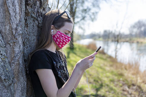 Girl with homemade protective mask using smartphone and leaning on tree - SARF04536