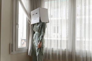Woman wearing a cardbox on head with bored smiley looking out of the window - AFVF06050