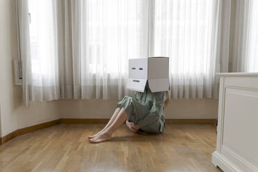 Woman wearing a cardbox on head with bored smiley and sitting on ground at home - AFVF06053