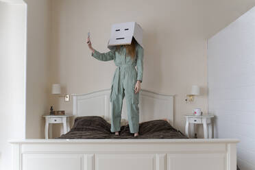 Woman wearing a cardbox on head with bored smiley taking a selfie on her bed - AFVF06068