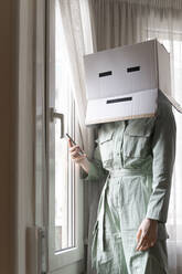 Woman wearing a cardbox on head with bored smiley looking out of the window and using smartphone - AFVF06071