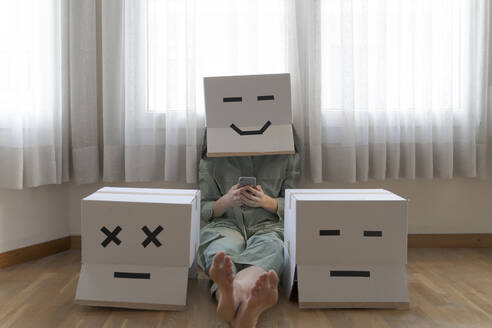 Woman wearing cardbox with smiling smiley and sitting between different cardboxes at home and using smartphone, smiling and bored cardbox - AFVF06077