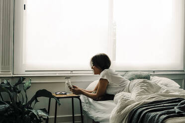 Woman lying in bed in the morning checking cell phone - ERRF03467