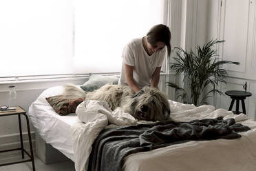 Happy mature woman cuddling her dog on bed - ERRF03476