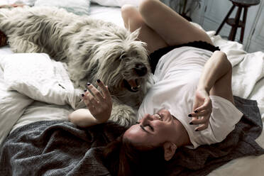 Mature woman lying on bed playing with her dog - ERRF03479