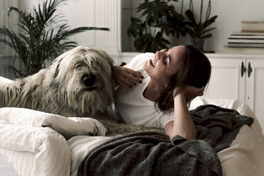 Laughing mature woman lying on bed having fun with her dog - ERRF03482