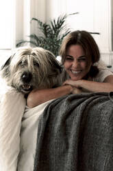 Portrait of laughing mature woman lying on bed with her dog - ERRF03485