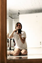 Mirror image of mature woman sitting on floor taking photo with camera - ERRF03491