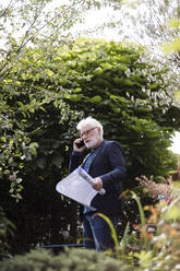 Senior man on the phone standing in garden with construction plan - JOSEF00256