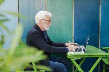 Senior man sitting at table outdoors using laptop - JOSEF00259