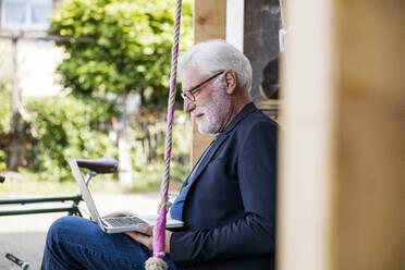 Senior man sitting outdoors looking at laptop - JOSEF00262