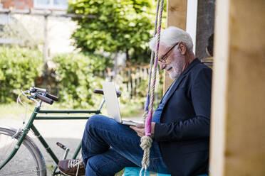 Senior man sitting outdoors looking at laptop - JOSEF00265