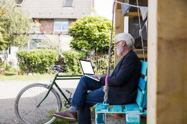 Senior man sitting outdoors looking at laptop - JOSEF00274