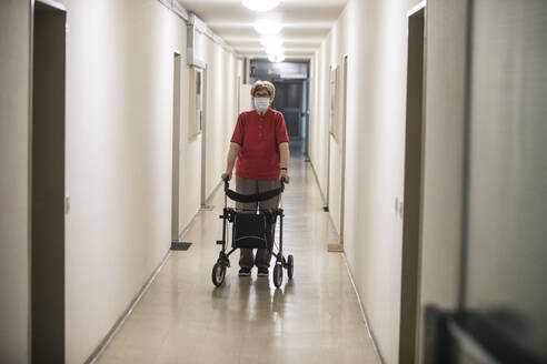 Senior woman wearing mask and walking with wheeled walker in corridor of retirement home - JATF01181