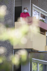 Senior woman wearing mask on balcony, retirement home - JATF01184