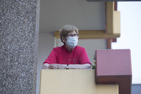 Senior woman wearing mask on balcony, retirement home - JATF01187