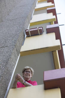 Senior woman on balcony, retirement home - JATF01190