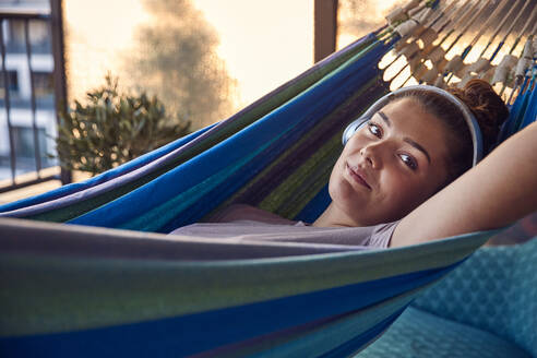 Portrait of smiling young woman lying on hammock on balcony listening music with headphones - JHAF00133