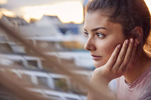 Pensive young woman on balcony looking at distance - JHAF00139