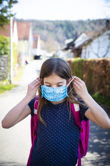 Girl with homemade protective mask on her way to school - LVF08832