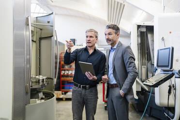 Businessmen in factory, having a meeting, using digital tablet - DIGF09837