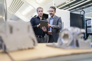 Businessmen in factory, having a meeting, using digital tablet - DIGF09840