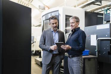 Businessmen in factory, having a meeting, using digital tablet - DIGF09849