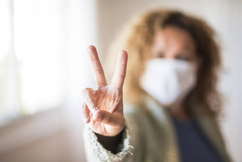 Woman with face mask making victory sign - SIPF02160