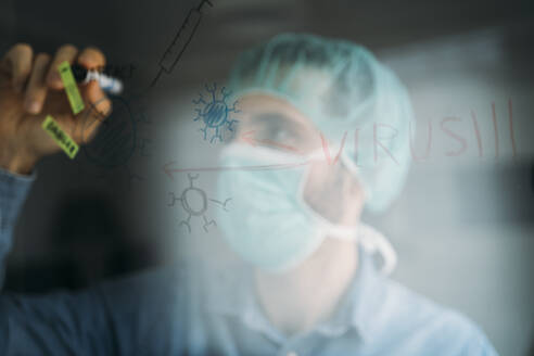 Businessman drawing coronavirus diagram on glass during quarantine period at home, Almeria, Spain, Europe - MPPF00861
