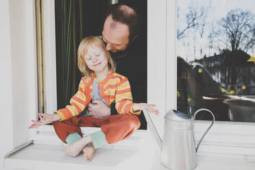 Father looking at daughter sitting on windowsill - IHF00333