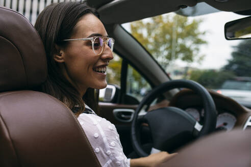 Smiling young woman driving convertible car in city - ABZF03095