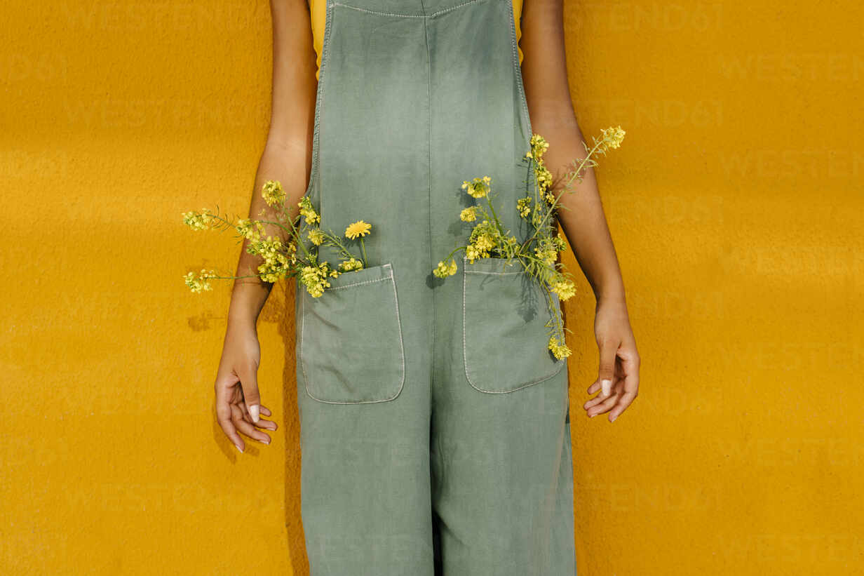 Midsection of woman wearing overalls with yellow flowers in pockets - TCEF00473 - Tania Cervián/Westend61