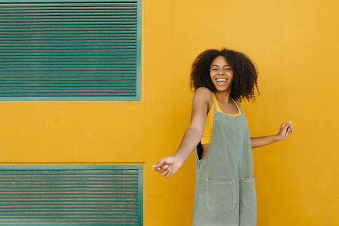 Portrait of happy young woman wearing overalls in front of yellow wall - TCEF00476