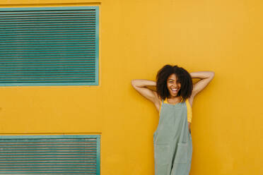 Portrait of happy young woman wearing overalls in front of yellow wall - TCEF00479