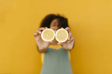 Close-up of young woman holding halved lemons - TCEF00482