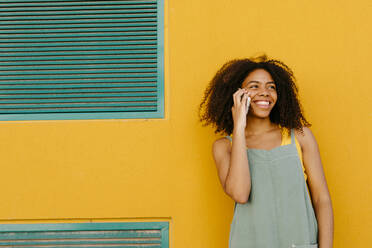 Portrait of happy young woman wearing overalls in front of yellow wall talking on the phone - TCEF00485