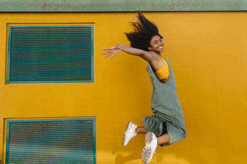 Portrait of happy young woman wearing overalls jumping in front of yellow wall - TCEF00497