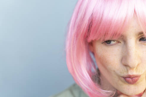 Portrait of young woman wearing pink wig pouting her mouth - AFVF06091