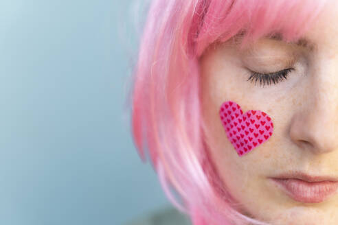 Young woman wearing pink wig with heart-shaped band-aid on her cheek - AFVF06094
