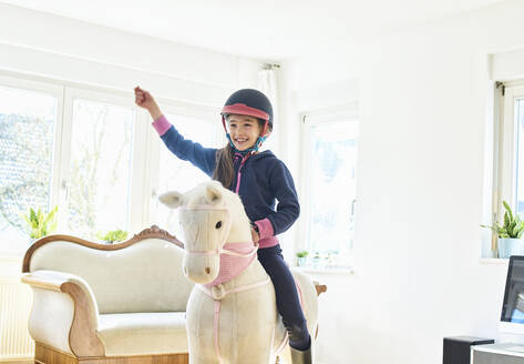 Girl riding on play horse at home - DIKF00460