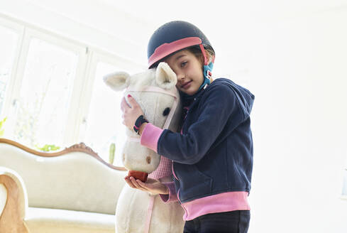 Girl cuddling her toy horse at home - DIKF00463