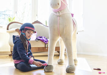 Girl grooming her toy horse at home - DIKF00466