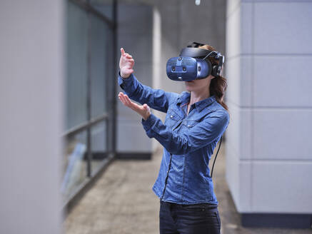 Woman wearing VR glasses and headset in modern office - CVF01592