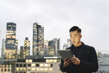 Man using tablet in front of urban skyline at dusk, Frankfurt, Germany - AHSF02254