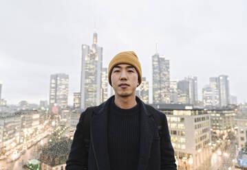 Portrait of stylish man in front of urban skyline, Frankfurt, Germany - AHSF02257