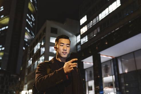 Man using smartphone in the city at night - AHSF02269