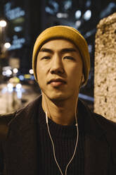 Portrait of stylish man with yellow hat and earphones in the city at night - AHSF02272