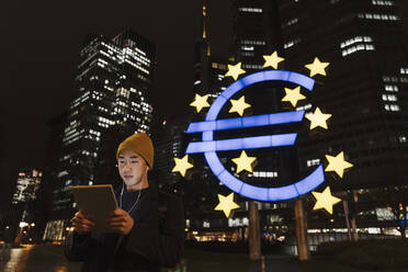 Man using tablet in the city at night with European Central Bank in background, Frankfurt, Germany - AHSF02275