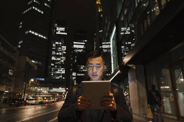 Man using tablet in the city at night - AHSF02281